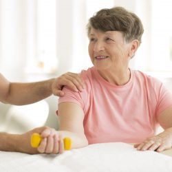 Professional physiotherapist helping smiling elderly woman holding yellow dumbbell